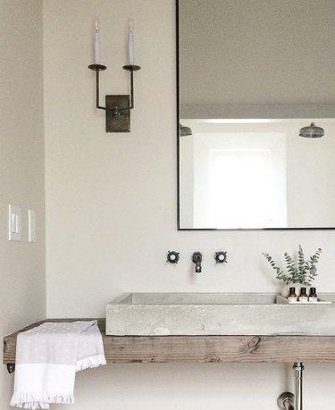 concrete bathroom sink in contemporary bathroom with wood countertop