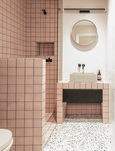 concrete trough bathroom sink in pink tiled bathroom with terrazzo flooring