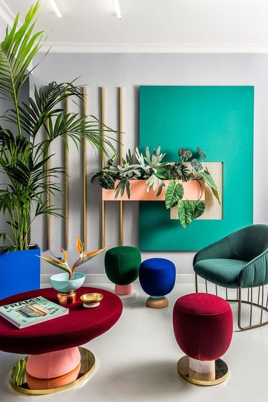 seating area with jewel-tone upholstered chairs, poufs, and tables