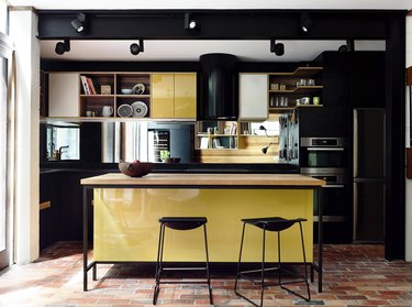 black and yellow cabinets with terra cotta kitchen flooring