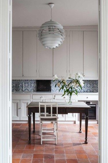 greige cabinets with patterned backsplash and terra cotta kitchen flooring
