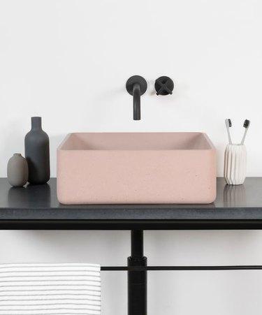 blush pink concrete bathroom sink with black fixtures