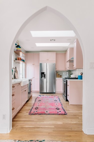 powder pink kitchen with bright pink rug and silver fittings