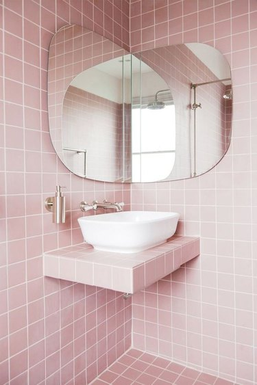 modern bathroom with pink tiles on walls, floor and countertops