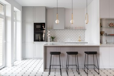 gray and white kitchen with brass fittings