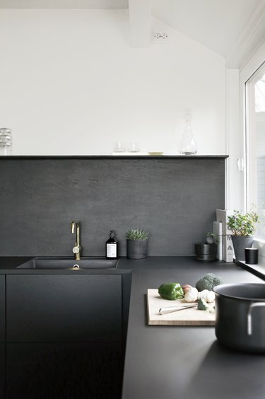 black and white kitchen with black backsplash and sink