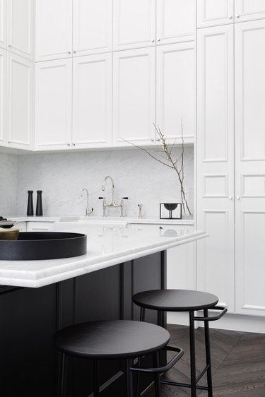 black and white kitchen with white cabinetry and black island and furniture
