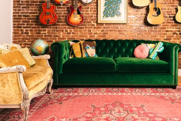 Tufted green velvet sofa in front of red brick wall and rosy area rug