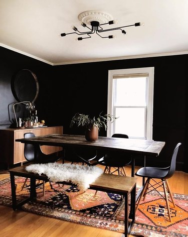 black dining room color idea with bright rug