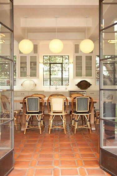 white kitchen with bistro dining chairs and terra cotta kitchen flooring