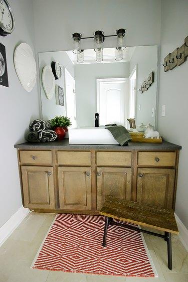 dark gray laminate bathroom countertop on rustic vanity cabinet in farmhouse bathroom