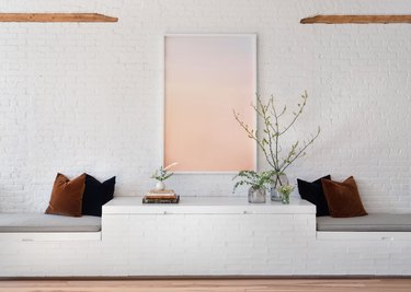 living room with built in bench seating and brick walls