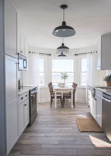 white rustic kitchen with dining nook and bay windows