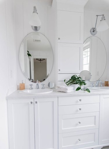 marble laminate bathroom countertop with white vanity cabinet and oval mirrors with wall sconces