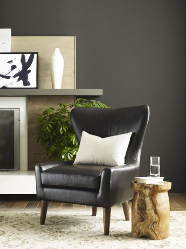 sherwin-williams urbane bronze paint color behind black armchair and wood stump side table