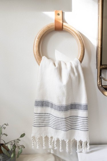 DIY wood and leather towel ring hanging on bathroom wall with Turkish hand towel