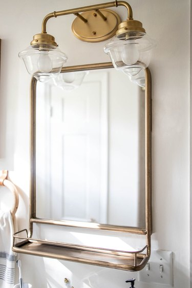 Brass two-arm lighting fixture above brass pharmacy-style mirror in bathroom