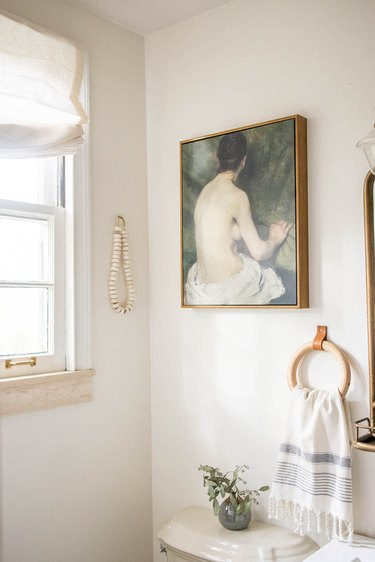 vintage oil painting on canvas hun in bathroom with wooden towel ring and bone beads
