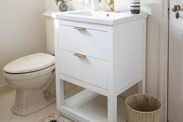 White bathroom sink vanity with brass handles
