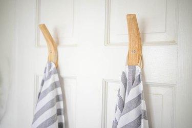 Two wooden towel hooks hung on door