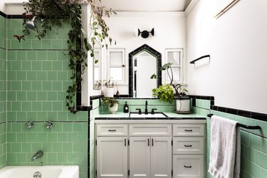 Green tile bathroom with plants