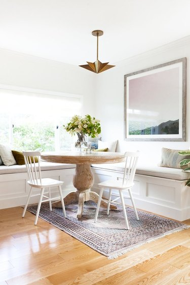farmhouse dining room space with white chairs and white bench seating