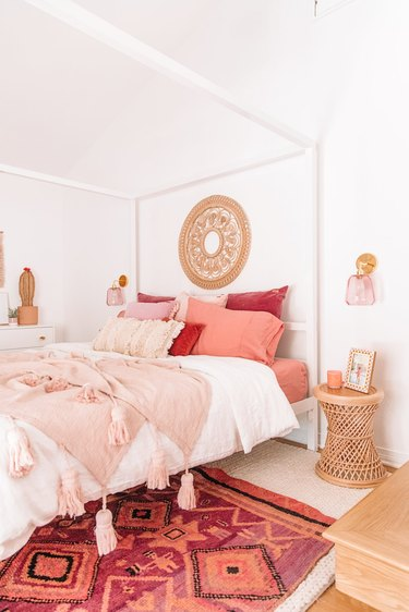 bohemian bedroom lighting idea with colorful pink wall sconces on either side of canopy bed