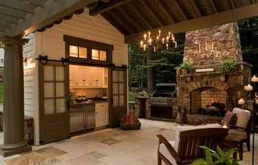 Double Contemporary Barn Doors, outdoor kitchen and fireplace, outdoor patio, arm chairs.