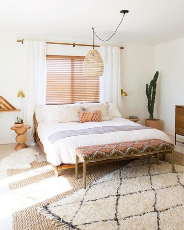 bohemian bedroom lighting idea with woven bamboo pendant hanging above bed