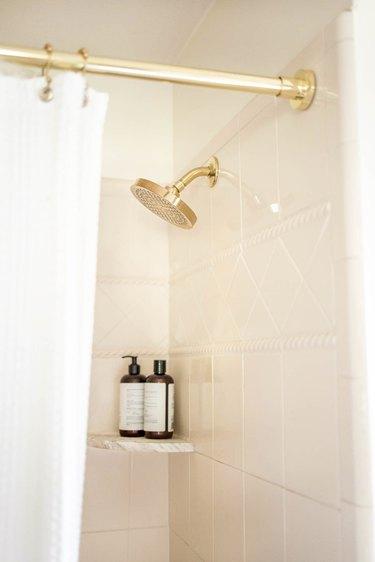 Brass shower head and shower rod in bathroom
