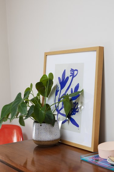 Plant in front of blue art on bedroom dresser