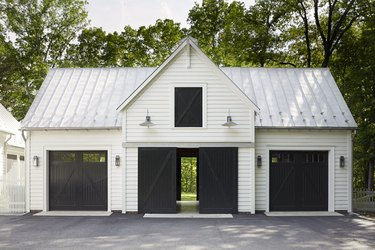 white house exterior with black carriage style garage doors