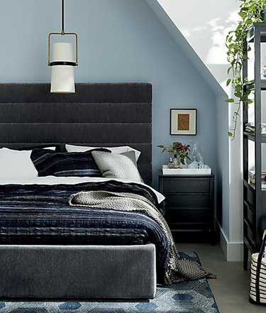 bedroom lighting idea with pendant hanging above bed with upholstered headboard