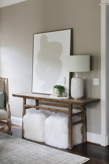 living room color idea with greige artwork and fluffy pouffes