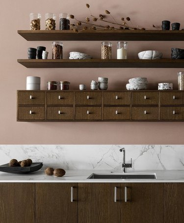 warm kitchen color idea with pink walls and wood shelving
