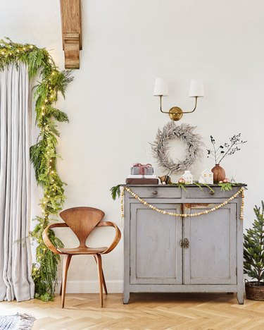 green and gold Christmas colors in living room vignette with cabinet, chair and decorations