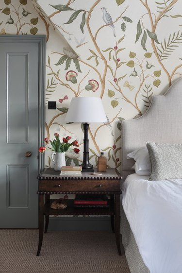 country bedroom idea with vintage bedside table with whimsical english country wallpaper