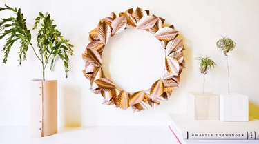 Rose gold wreath next to leather-wrapped vase with greenery