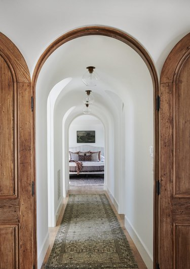 Endless arches and a long runner make this hallway seem infinite.