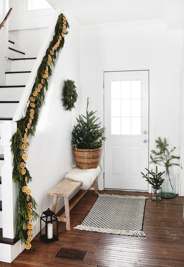 white and green Christmas colors in entryway with garlands and mini tree by the stairs