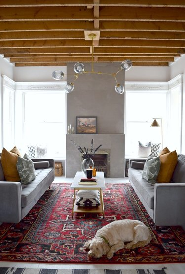 living room lighting idea with bubble chandelier over coffee table mounted to wood beam ceiling
