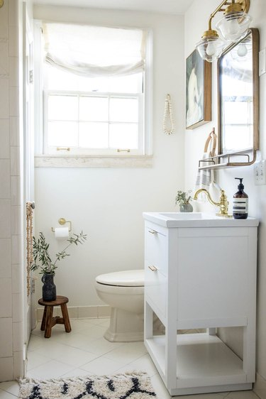 Small bathroom with Walmart white vanity sink and brass mirror and sconces