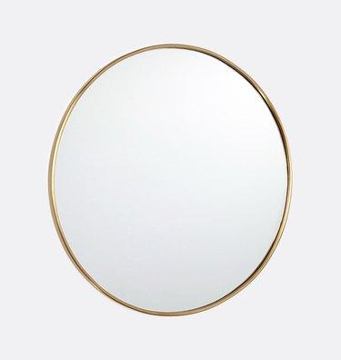 Round mirror with thin brass border
