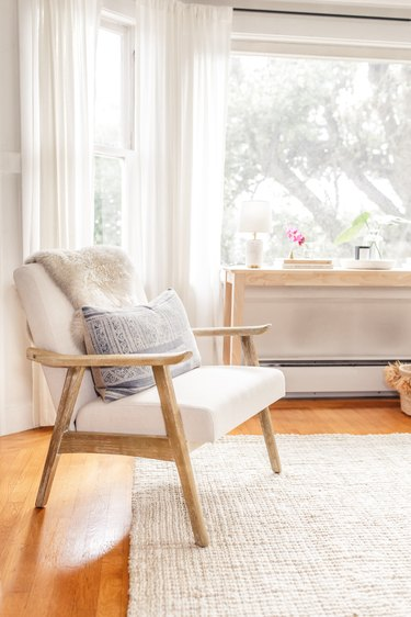 Scandinavian living room with white chair draped with faux fur and sheer drapery
