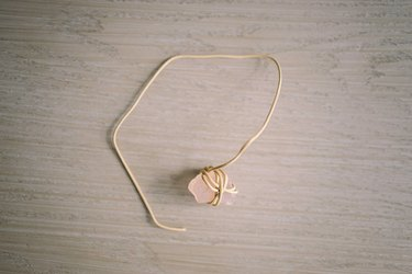 Leather cord tied and wrapped around small pink crystal