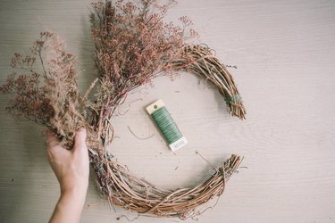 Tying dried floral bundles onto grapevine wreath with floral wire