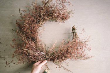 Attaching dried floral bundles to bottom half of crescent wreath