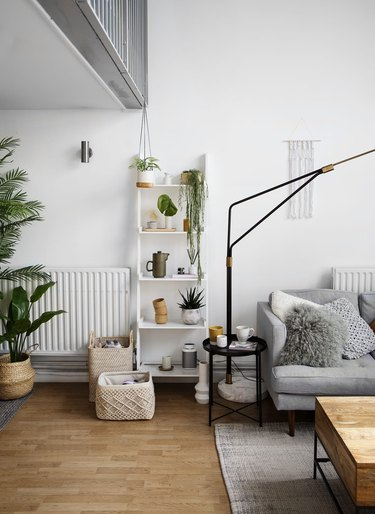 Scandinavian living room with white leaning bookcase next to floor lamp and gray sofa