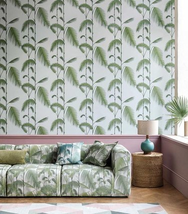 living room wallpaper idea with palm print to match sofa fabric above pink wainscoting