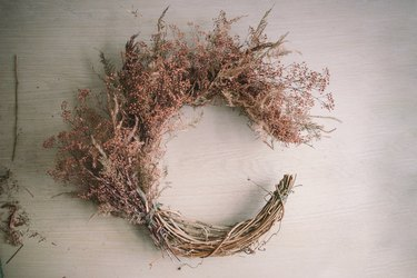 Top half of crescent wreath filled with dried floral bundles